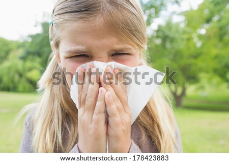 Close-up portrait of a young girl blowing nose with tissue paper at the park