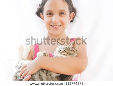 Close up portrait of a young girl holding a cat in her arms and smiling at the camera.