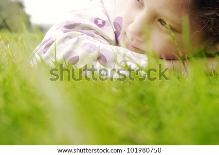 Close up portrait of a young girl laying down on green grass in the park, looking away. - stock photo