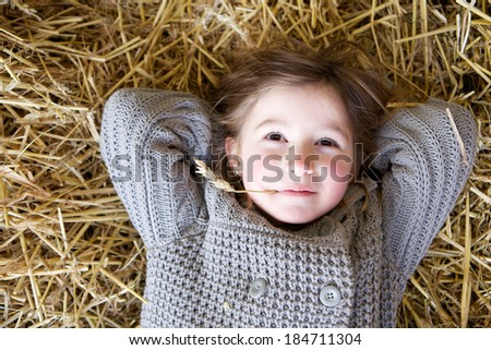 Close up portrait of a young girl lying down on hay and daydreaming  - stock photo