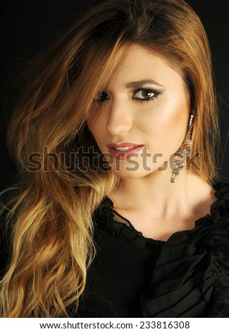 close up portrait of a Young gorgeous long haired blond girl wearing evening make up and long earrings - stock photo