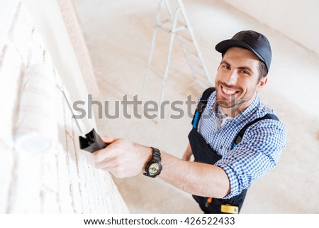 Close-up portrait of a young handsome builder using paint roller in his work indoors