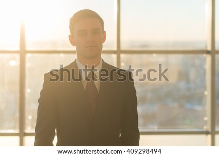Close-up portrait of a young handsome businessman, looking seriously at camera, standing in light office over the large window background. - stock photo