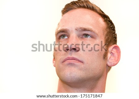 Close-up portrait of a young handsome Caucasian blond man with blue eyes, looking up with trust and determination, isolated on white background