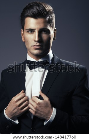 Close-up portrait of a young handsome man with bow tie - stock photo