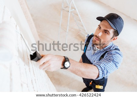 Close-up portrait of a young handsome worker using paint roller at the working area - stock photo