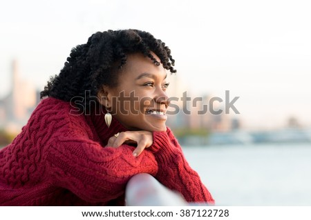 Close up portrait of a young happy african woman leaning on the banister of a bridge near river. Happy young african woman at river side thinking. Smiling pensive girl looking across river at sunset.  - stock photo
