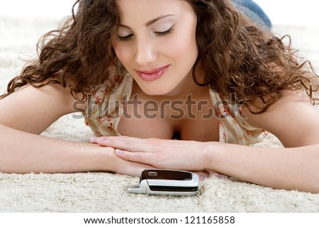 Close up portrait of a young hispanic woman laying down on a furry carpet at home, looking at her cell phone and waiting for it to ring.