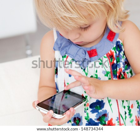 Close up portrait of a young infant girl holding and using a smartphone cell phone being focused while standing in a living room at home, interior. - stock photo