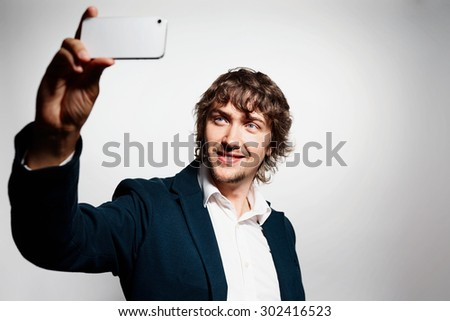 Close up portrait of a young joyful man holding a smartphone digital camera with his hands and taking a selfie self portrait of himself standing against grey background