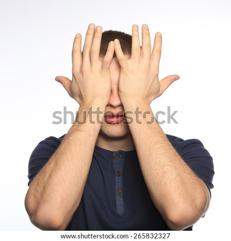 close-up portrait of a young man closing his eyes with his hands on a white background studio