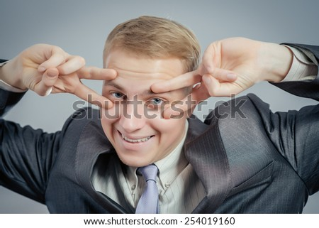 Close-up portrait of a young man covering face with his hands with enough space to look through the isolated gray background. Negative human emotions facial expression feelings, reactions. - stock photo