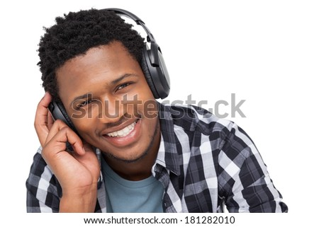 Close-up portrait of a young man enjoying music over white background - stock photo