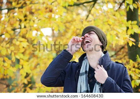 Close up portrait of a young man holding hat laughing outdoors  - stock photo