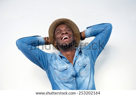 Close up portrait of a young man laughing with hands behind head on white background - stock photo