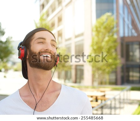 Close up portrait of a young man laughing with headphones - stock photo