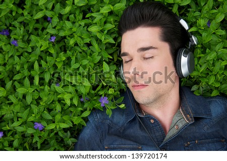 Close up portrait of a young man lying on grass with headphones and eyes closed - stock photo