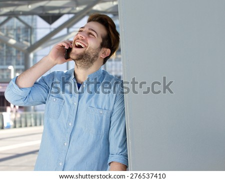 Close up portrait of a young man talking on mobile phone and laughing - stock photo