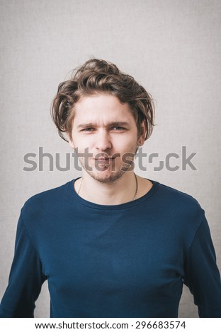 Close up portrait of a young man with a confused face - stock photo