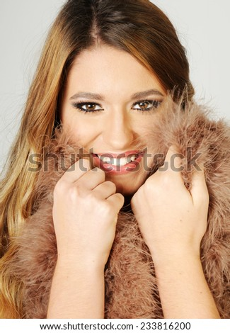 close up portrait of a Young sensual beautiful smiling girl posing with fur coat close to her face with perfect make up - stock photo