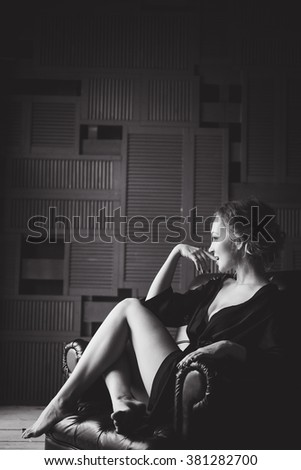 close-up portrait of a young slim sexy girl in black lingerie sitting on a chair laughing cozy home posing with shapely legs and graceful hands - stock photo