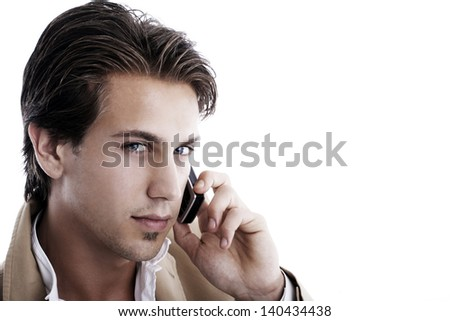 Close-up portrait of a young sophisticated businessman talking on a mobile phone on a white background looking at the camera