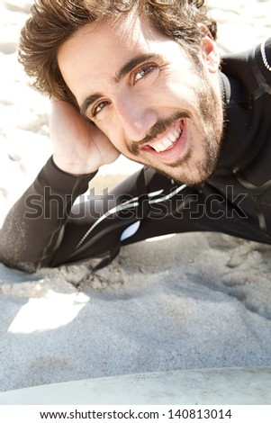 Close up portrait of a young sport surfing man laying down and relaxing next to his surfing board while on a white sand beach during a sunny day, smiling at camera. - stock photo