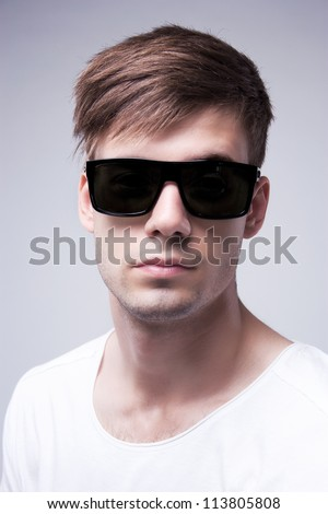 Close-up portrait of a young stylish beautiful  man with black glasses on a grey background - stock photo