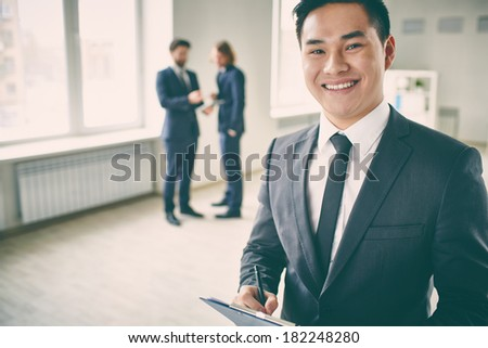 Close-up portrait of a young successful manager with clipboard posing at camera while his colleagues talking on the background  - stock photo