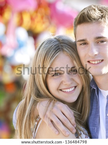 Close up portrait of a young teenage couple hugging while enjoying being together in a funfair ground with game and color around them, smiling. - stock photo