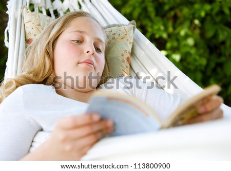 Close up portrait of a young teenage girl reading a book while laying down on a hammock in a garden. - stock photo
