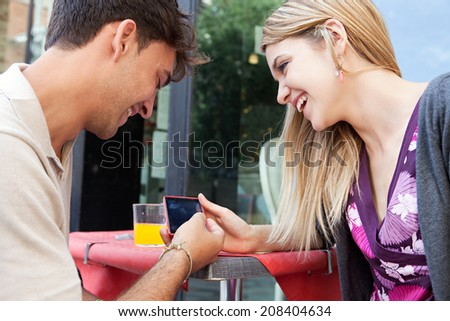 Close up portrait of a young tourist couple sitting together at a cafe terrace with refreshments sharing a smartphone while networking, visiting a destination city. Technology and travel lifestyle. - stock photo