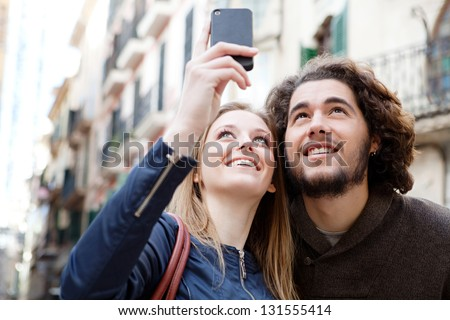 Close up portrait of a young tourist couple visiting a destination city and taking pictures of the classic buildings while on vacation in Europe.