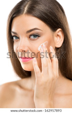 Close-up portrait of a young woman applying cream on her face over a white background