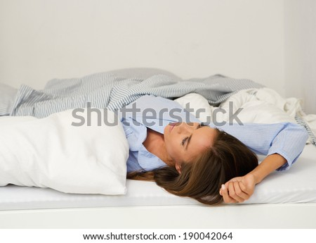 Close up portrait of a young woman awake in bed with insomnia