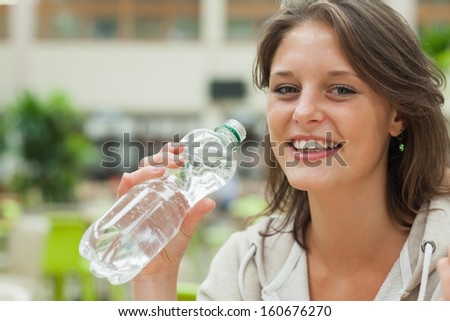 Close-up portrait of a young woman drinking water against blurred background - stock photo