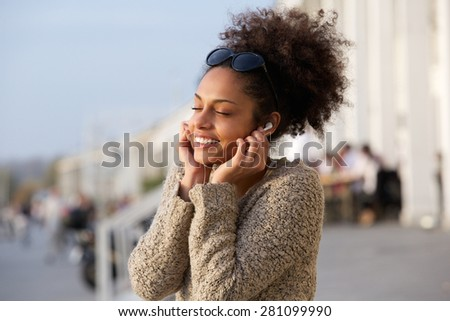 Close up portrait of a young woman enjoying music on earphones - stock photo