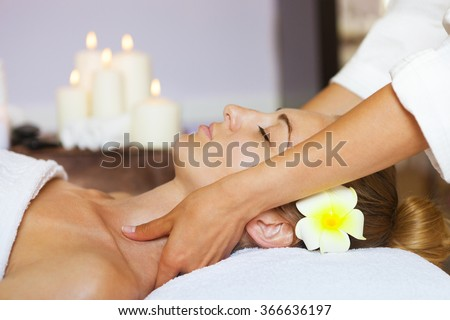 Close up portrait of a young woman getting spa treatment. Face massage