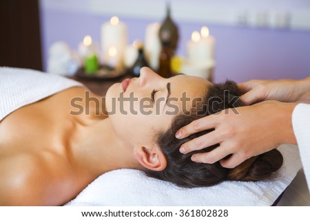 Close up portrait of a young woman getting spa treatment. Head massage - stock photo