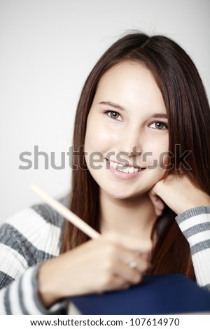 close up portrait of a young woman holding a pencil with a large pile of books in font of her - stock photo