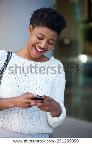 Close up portrait of a young woman laughing and reading text message on cellphone - stock photo