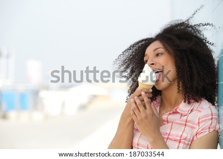 Close up portrait of a young woman licking ice cream outdoors in summer  - stock photo