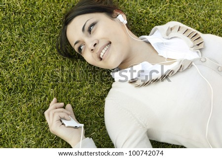 Close up portrait of a  young woman listening to music on her mp4, laying down on green grass, smiling. - stock photo