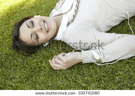 Close up portrait of a  young woman listening to music on her mp4, laying down on green grass in a park with her eyes closed. - stock photo