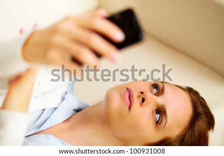 Close up portrait of a young woman lying on sofa and using a cellphone while thinking - stock photo