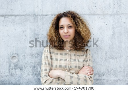 Close up portrait of a young woman posing outdoors with arms crossed - stock photo