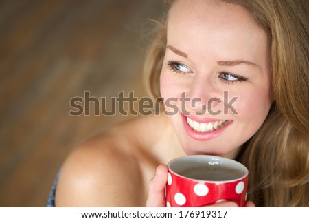 Close up portrait of a young woman smiling and  enjoying a cup of tea at home