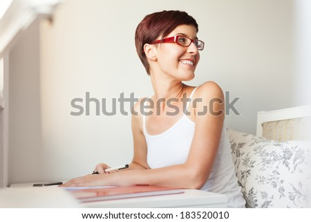 Close-up portrait of a young woman smiling and sitting at the table,having a break from preparing exams. - stock photo