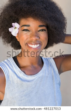 Close up portrait of a young woman smiling with afro hair against  background
