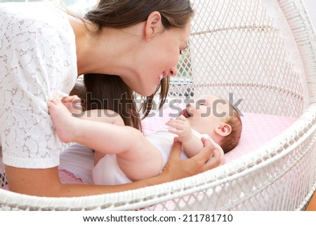 Close up portrait of a young woman smiling with newborn infant - stock photo